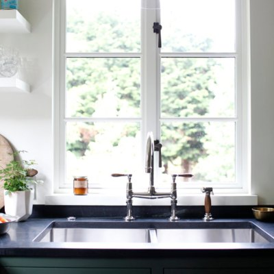 Best kitchen sink materials Kitchen sink with stainless faucet, window, pendant light, open shelves, plant, black counters, green cabinets.