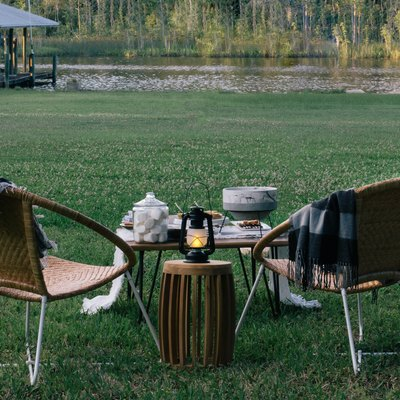 Two lawn chairs in the foreground with a table set up with a s'mores station; a lush green lawn with a river in the background