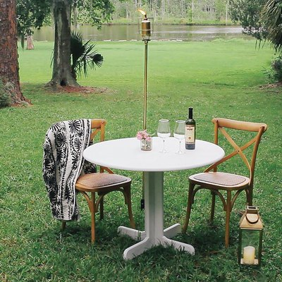 A small table and chairs with a bottle of wine and two glasses; a green lawn with trees and a river in the background