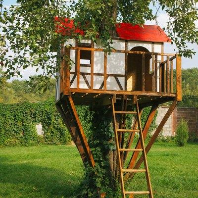 Cute small tree house for kids on backyard.