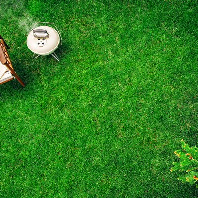 Ivory colored grill on the grass near the wooden armchair with a book and glasses. Top view