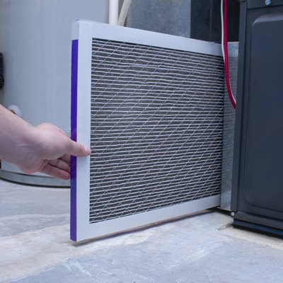 A person changing an air filter on a high efficiency furnace