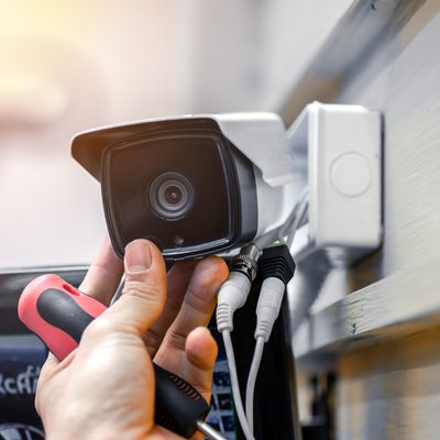 Close-up of surveillance camera installation, male hand holds cctv camera