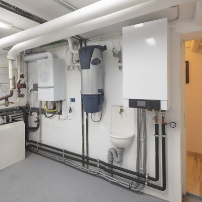 Technical room. Modern home, steam water heating system, gas boiler for central heating and cooling and hoover, vacuum cleaner machinery.