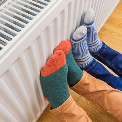 Woman and child wearing colorful pair of woolly socks warming cold feet in front of heating radiator in winter time. Electric or gas heater at home.