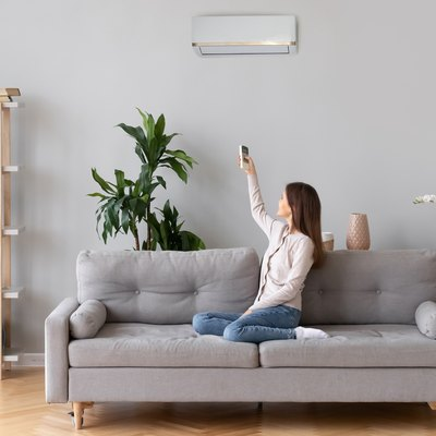 Young woman switching on air conditioner sitting on couch