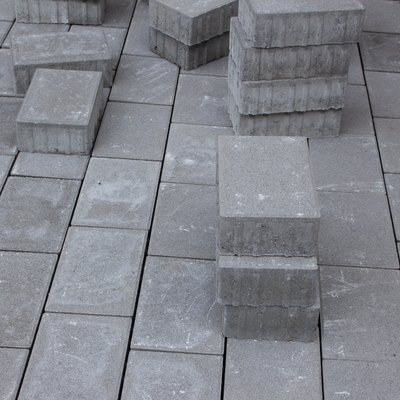 Concrete paver blocks laid beside a building, some paving stones are stacked for future use