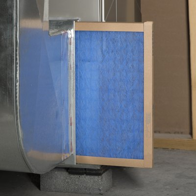 A furnace filter in the process of being replaced.