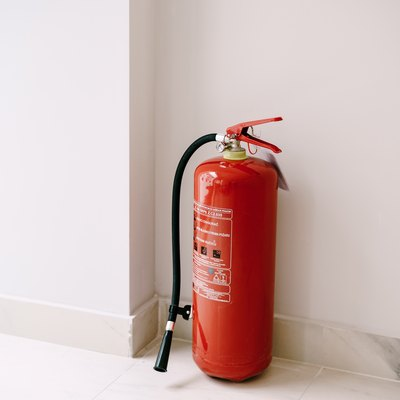 A close-up of a red fire extinguisher on the floor in the corner against a white wall.