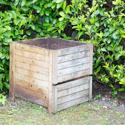 composter in the garden filled with freshly cut grass