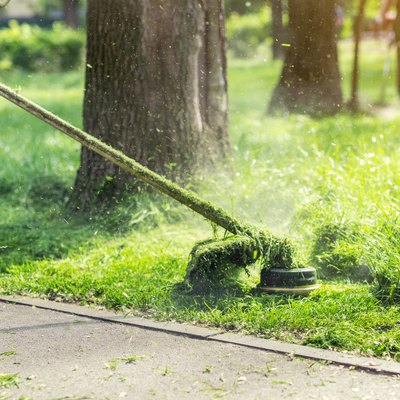 Worker mowing tall grass with electric or petrol lawn trimmer in city park or backyard. Gardening care tools and equipment. Process of lawn trimming with hand mower