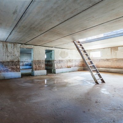 Concrete interior of unfinished garage basement apartment building trash colour with ladder and dlue day window light