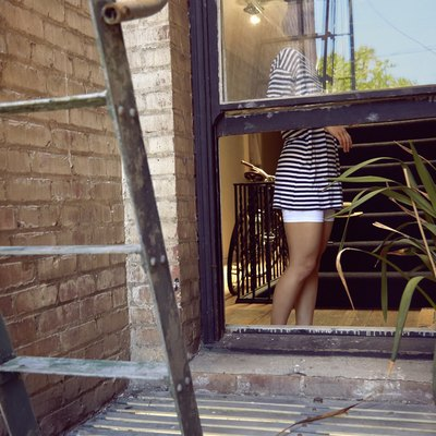 Young woman standing near window next to fire escape