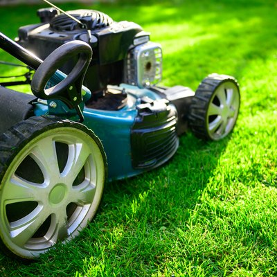 Lawn mower on green grass in a sunny day.