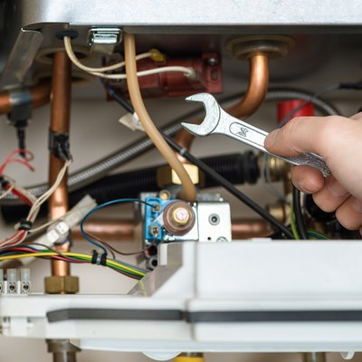 Technician is holding wrench in front of combi gas boiler