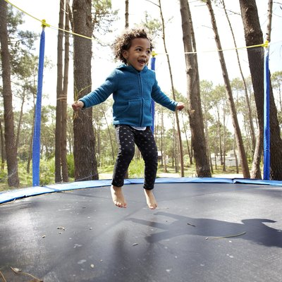 Mixed race girl jumping on trampoline