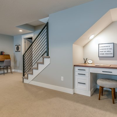 Basement rec room with home office desk underneath the stairs