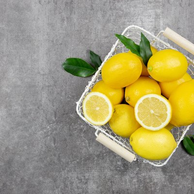 Fresh lemons with leaves in a basket on dark background. Vitamin C concept, immune defence.Top view. Copy space.