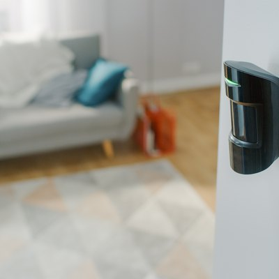 Close Up Object Shot of a Modern Movement Detector Unit on a White Wall in a Cozy Apartment in the Background.