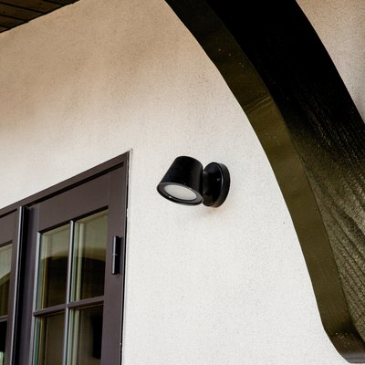 A black flood light on a Spanish-style home