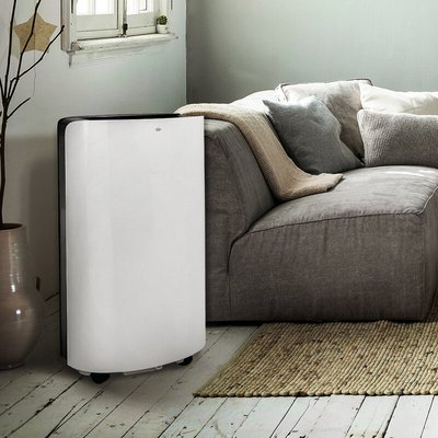 A white portable A/C in a living room with a gray couch and light wood floors