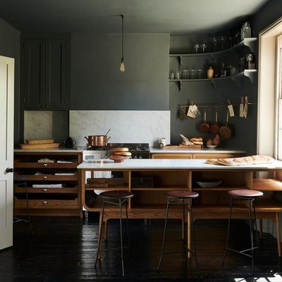 unfinished oak cabinets in kitchen with dark green walls and ceiling