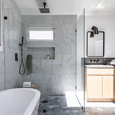 A gray bathroom with a glass shower door, a freestanding tub, and a light wood vanity with two mirrors