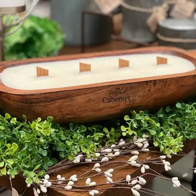 A citronella candle in a wood basin