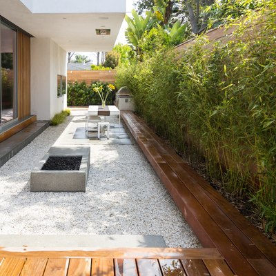 A backyard with a small fire pit surrounded by gravel and wood benches