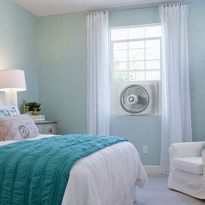 Reversible white fan installed in window of aqua and white bedroom
