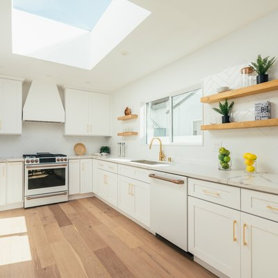 White cabinets with gold handles, skylight, wood flooring in a minimalist kitchen