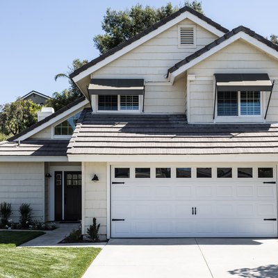 A suburban house with white trim and a white garage door; lush green grass in the front yard