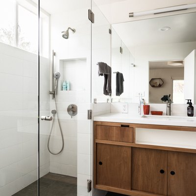 White bathroom with glass shower walls and brown cabinets