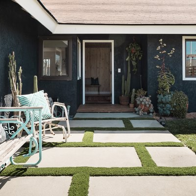 a yard with stone pavers with grass in between, plants are in a garden nearby