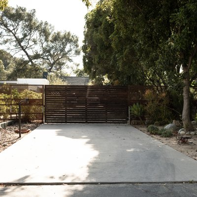 concrete slab in the backyard, a horizontal wood fence, orange pots, large trees in the background