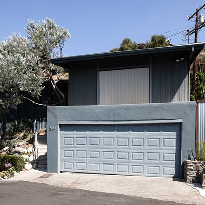 Gray house with a large garage, wood and corrugated metal fence, stone planters, and trees.