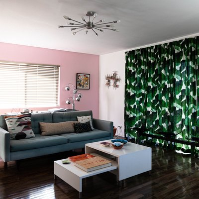 A pink living room with palm leaf curtains and blinds over the window