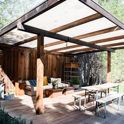 A wood pergola with wood flooring, dining bench and sofa seating
