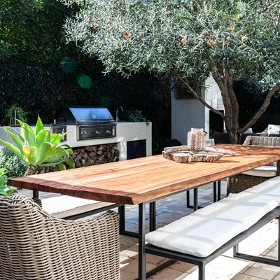 A wood table with benches and wicker chairs on a patio