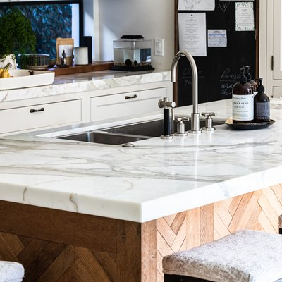 A wood kitchen island with white granite countertops in a white cabinet kitchen