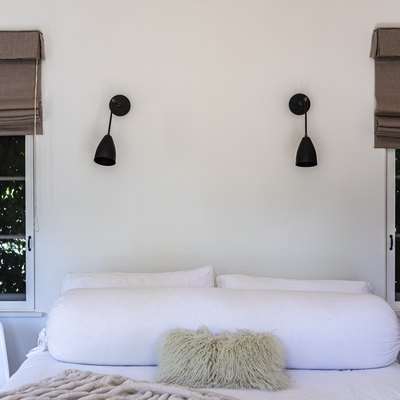 A bedroom with white bedding and windows with brown shades