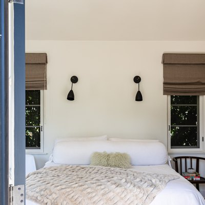 A bedroom with two windows covered with shades