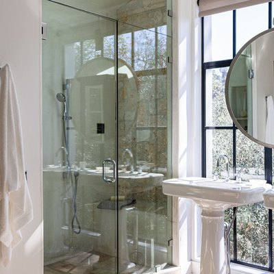 Bathroom with large windows, porcelain sinks, large mirror and glass door shower