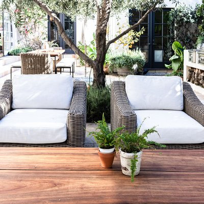 Patio wicker chairs with white cushions with a wood table and plants