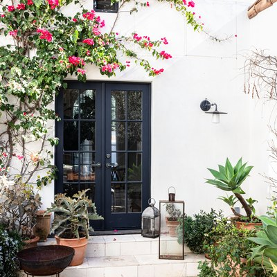 Black French doors on a white Mediterranean styled home with plants and trees