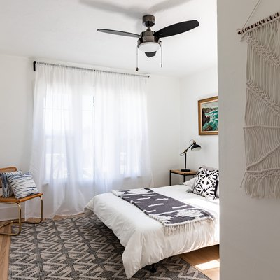 A bedroom with a macrame hanging and sheer curtains hung