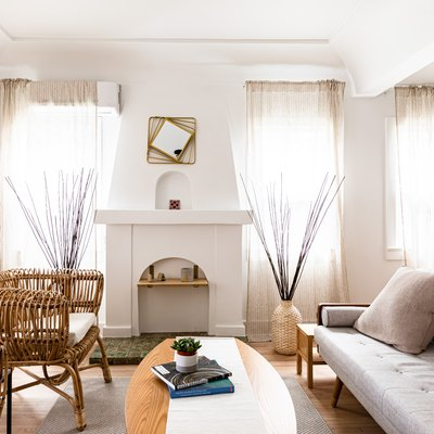A living room with sheer draperies on every window