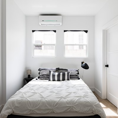 Minimalist white walled bedroom with white bedding and black accents