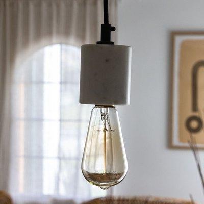 An exposed incandescent light bulb pendant light in a boho living room