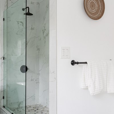 A glass shower in a white walled bathroom with a woven plate wall hanging